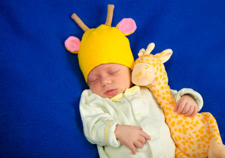 Cute newborn baby lying on a blue blanket with toy giraffe. Determine the of the baby. Boy or girl.