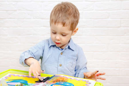 Cute young kid boy drawing or painting fingers. Kindergarten children education, back to school, or preschool child study at home concept
