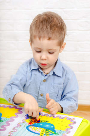 Adorable young child boy drawing or painting fingers. Kindergarten children education, back to school, or preschool child study at home concept