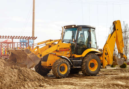 Working excavator tractor digging a trench for pipenlineat at construction site. Digger machine digging and removing earth