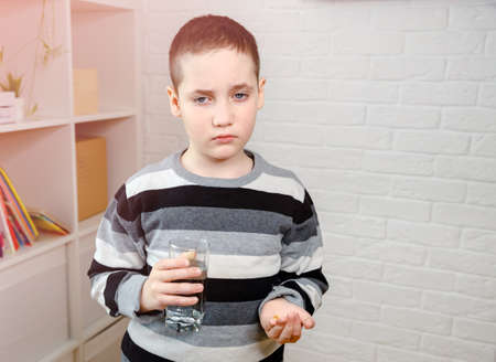 Adorable little boy with a sad face turns away, unwilling to take the medicine pill being offered