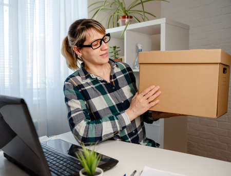 A woman works remotely from home. Making orders online, delivery of goods. Online shopping, ecommerce and delivery service concept. Paper carton, depicts customers order things from retailer sites via the internet