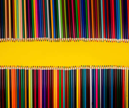 Color pencils on yellow background. Overhead shot of stationery on paper. Frame of school office supplies