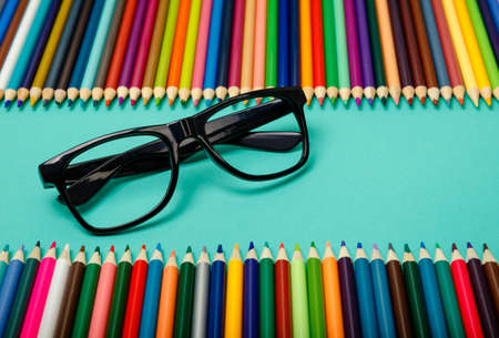Back to school. Office background. Color pencils, glasses on blue background. Close up. Top view, layout, flatly