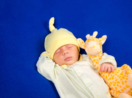 Lovely newborn baby lying on a blue blanket with toy giraffe. Determine the of the baby. Boy or girl. The concept of pregnancy, expectancy and problems