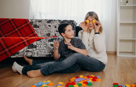 Young happy mom and schooler son sit on floor, playing with toy blocks together, mother and little boy child have fun engaged in funny activity game at home. Concept of distance education Archivio Fotografico