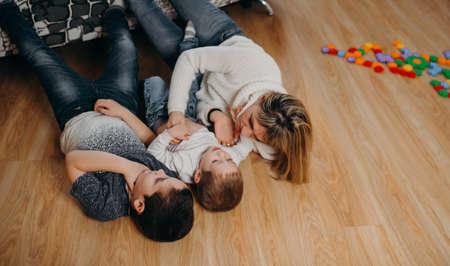 Maman et ses fils jouent par terre. Elle les serre dans ses bras et les caresse doucement. La famille s'amuse ensemble pendant le confinement. Coups de pied photo
