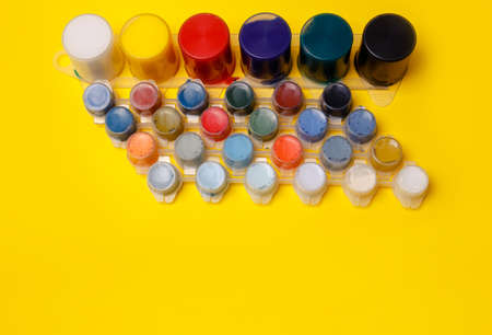 Multi-colored paints for drawing pictures and drawings. Finger paints. Concept for artists, art schools. Back to school. Education yellow background. Top view