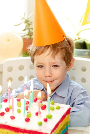 Birthday child looking at candles on birthday rainbow cake, making a wish before blows them out at birthday party. Birthday cake with candles, bright lights bokeh.Celebration