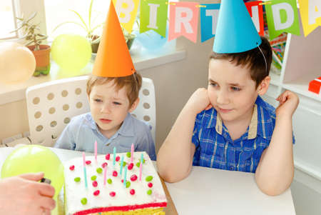 Two beautiful kids boys in birthday hats looking at camera and smiling at birthday party. Colorful background with balloons and birthday rainbow cake Imagens