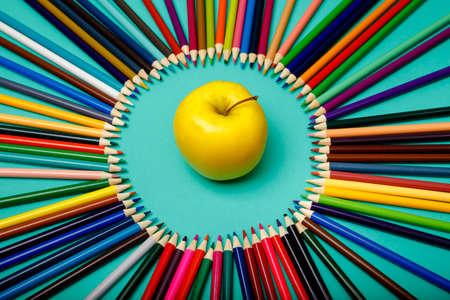Apple and colored pencils are laid out in a circle on blue background. Back to school. Office background. Top view, layout, flatly Foto de archivo