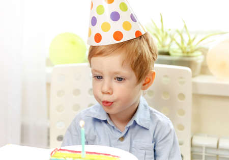 Beautiful child makes a wish and blows out the candle at birthday cake. Birthday party