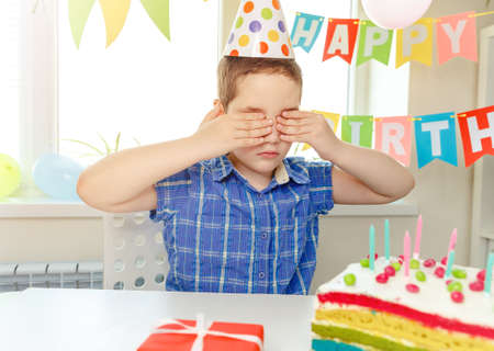 Funny boy in birthday cap smiling, close her eyes, make a wish, surprise a birthday cake with candles. Child celebrates her birthday alone