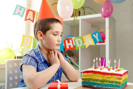 Happy boy with funny face near birthday rainbow cake. Festive colorful background. Good birthday party. Birthday party