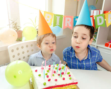 Beautiful kids celebrating birthday and blowing candles on homemade baked cake, indoor. Birthday party for siblings. Birthday party and gifts concept