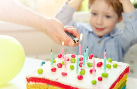 Kids birthday party. Child blowing out candles on colorful cake. Decorated home with rainbow flag banners, balloons. Little boy celebrating birthday. Party food
