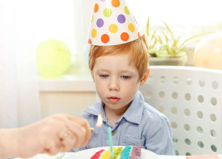 Child is dreamily smiling and looking at birthday rainbow cake. Festive colorful background with balloons. Birthday party and wishes concept