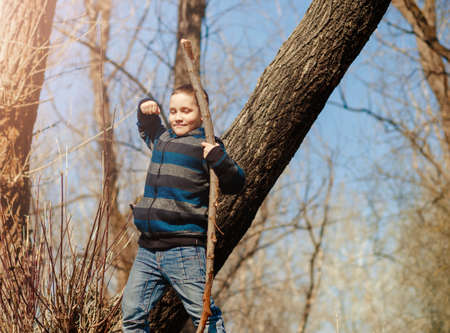 Funny child with a stick in the role of a victorious warrior in the spring forest in the fresh air. Concept of active recreation and unity with nature
