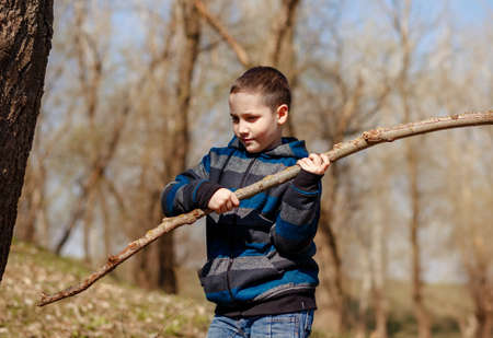 Pretty boy playing with a stick in the spring forest in the fresh air. Concept of active recreation and unity with nature