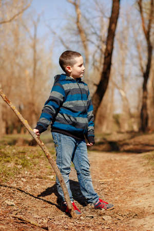 Funny child playing with a stick in the spring forest in the fresh air. Concept of family recreation and active lifestyle Фото со стока
