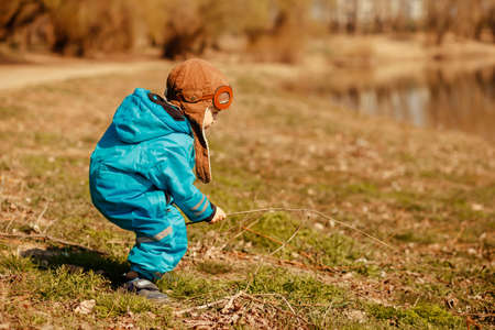 Funny kid playing on the Bank of the river in the fresh air. Concept of family recreation and active lifestyle