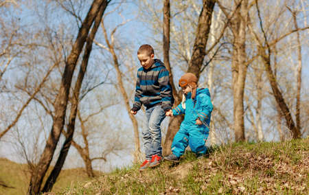 Happy children on the walk in sunny forest or park. Spring and summer outdoor activities, happy childhood concept