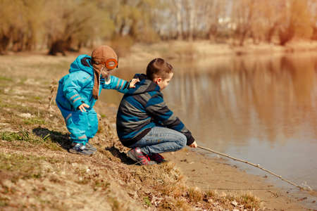 Two friendly brothers on the river Bank look at the water and the wonderful landscape. Fishermen catch fish. Family vacation concept Фото со стока