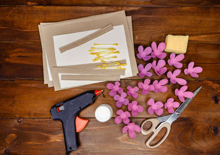 Kid makes Mother's Day or Birthday greeting card. DIY holiday card with pink paper volumetric flowers. Handicraft made by child with scissors, glue and paper. layout. Step 5 of 7