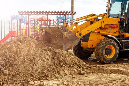 Yellow excavator in sunlight. Digger machine digging and removing earth adjusting ground level in construction site Imagens