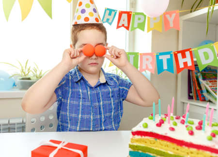 The boy put the balloons to his eyes. Festive atmosphere at home. The day of the birth. Birthday party and cake Imagens