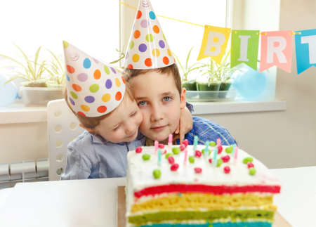 Friendly two boys embrace and have good relationship. Kids celebrate birthday together in living room. Birthday cake. Embracing. Children enjoy holiday, special occasion Imagens