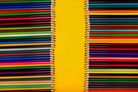 Abstract background from set of color pencils for drawing. Back to school, Close up color pencils on yellow background. Flatly. Copy space for Text
