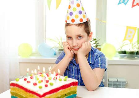 Funny child smiling in birthday cap, a birthday cake with candles. Child celebrates her birthday. Happy birthday