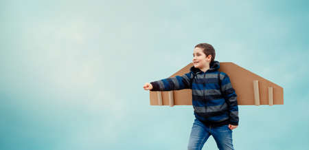 Cute child with toy paper wings airplane against blue sky background outdoors. Concept of successful business development and teamwork