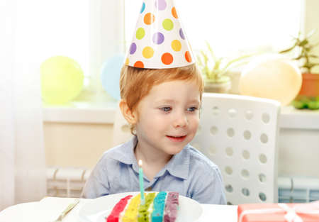 Little boy sits thoughtfully and dreamily at festive table near birthday rainbow cake and makes a wish. Colorful background. Birthday party