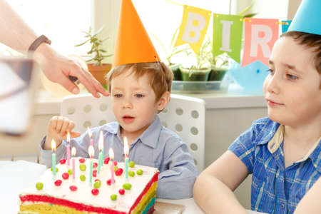 Kids birthday party. Child blowing out candles on colorful cake. Decorated home with rainbow flag banners, balloons, confetti. Little boy celebrating birthday. Party food