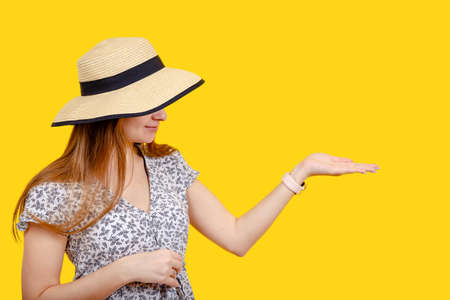 Handsome girl in a straw hat held out her hand with space for text, advertising, summer discounts, special offers for selling goods. Banner