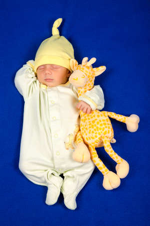 Pretty baby sleeping on a blue blanket. Little boy in pajamas taking a nap with toy giraffe. Bed time for kids