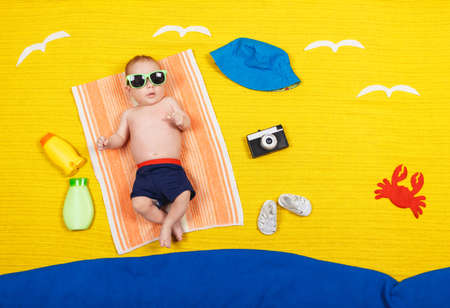 Cute child in swimming trunks is lying on a towel. Nearby are UV sunscreen, panama hat, glasses, crab, sandals and camera crab. Dreams of sea, adventures and travel. Summer vacation and travel concept Stok Fotoğraf