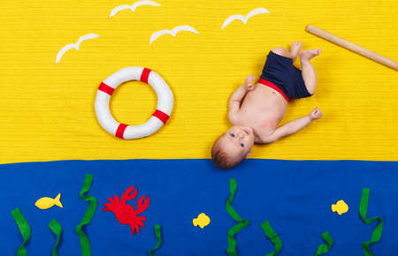 Baby boy is diving into imaginary pool. Dreaming about sea, adventures and travel, summer vacation and travel concept. Funny little child imitating swimming and jumping into the water at home