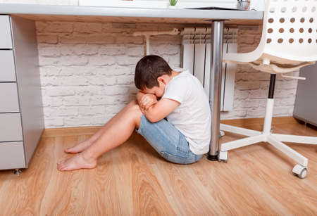 Schoolboy torturing of bullying. Teen boy sitting on on floor under the desk in the nursery. Teenager one cries. Problem of the relations of parents and children