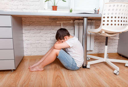 Sad and unhappy child sitting on floor under the table. Upset toddler boy in the nursery. Problem child. Family conflict. Concept for bullying, depression stress or frustration. Back to school.