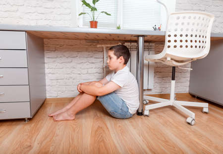 Offended upset boy teenager sitting on the floor. Schoolboy torturing of bullying. Teen boy sitting under the desk in the nursery. Teenager one cries. Problem of the relations of parents and children Foto de archivo