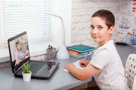 Child attending to online school class. Online child education. Learning from home, homeschooling, home school kid concept. Covid-19, coronavirus, quarantine and social distancing concept. New normal