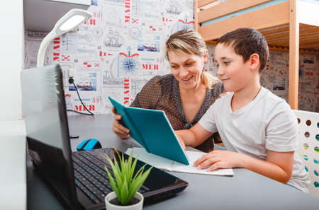 Schoolboy educate online. Mother helps his son with homework. Boy in video conference with teacher on laptop at home. Homeschooling and distance learning. Quarantine and social distancing concept
