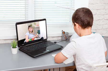 Boy is having a video lesson conference laptop with a teacher at home. School boy is studying. Home schooling. Online child education. New normal. Covid-19, coronavirus. Social distancing. Stay home