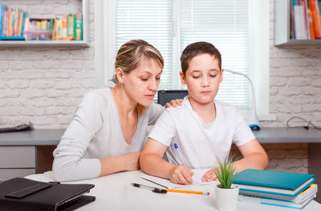 Mother helps son to do lessons. Home schooling, home lessons and distance learning. The tutor is engaged with the child, teaches to write and count. Quarantine and social distancing concept