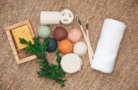 Natural organic and biodegradable products for face and body care. Bamboo toothbrushes, konjac sponge, natural organic products. Plastic free, zero waste cosmetics, flat lay. Overhead shot