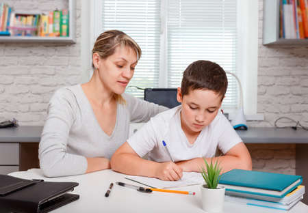 Mother helps son to do lessons. The tutor is engaged with the child, teaches to write and count. Online child education, home schooling, home lessons. New normal. Coronavirus. Social distancing