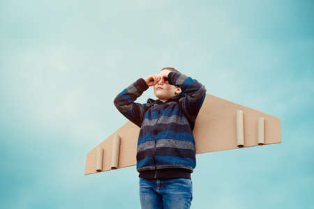 Happy child playing outdoors. Kid having fun against blue sky background. Child with toy paper wings airplane. Kid pretend to be pilot. Travel, summer vacation, holidays and freedom concept